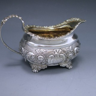 A GEORGE III ANTIQUE SILVER CREAM JUG