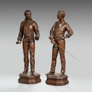 An unusual pair of walnut carved fencers