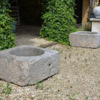 A pair of square granite planters