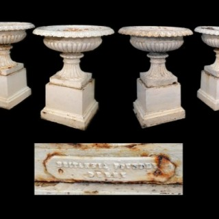 A set of four mid 19th century cast iron terrace garden urns on square plinths