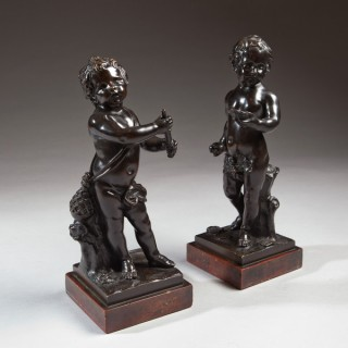 A PAIR OF BRONZE CHERUBS ON MARBLE BASES