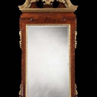 A GEORGE II PARCEL GILT AND BURR WALNUT MIRROR