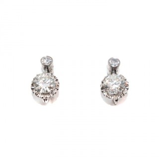 A pair of drop brilliant cut diamond earrings in white gold mounts.
