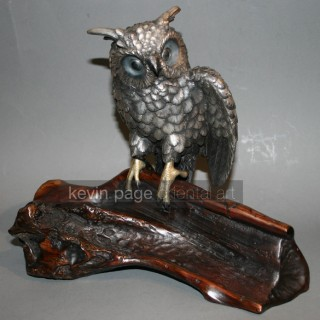 A silvered owl on a wood stand