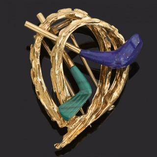 Gold hooped chip brooch with crossed gold clubs, laspis and malachite.