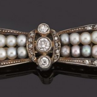 Natural pearl and diamond Bow brooch in Platinum and gold.