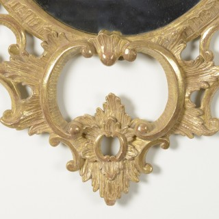 A pair of George III carved giltwood oval mirrors