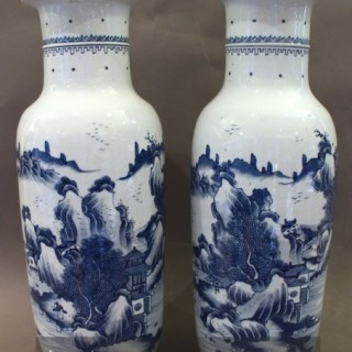 a pair of chinese blue and white vases decorated with a wrap-around design of a mountain landscape