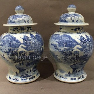 a pair of chinese blue and white temple jars with a landscape scene
