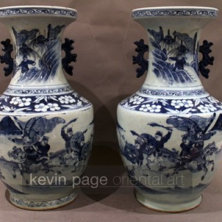 a pair of chinese blue and white vases decorated with a battle scene
