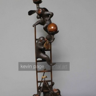 an unusual japanese candlestick in the form of monkeys up a ladder