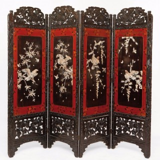 A four panel mother of pearl mounted ebonised wood screen
