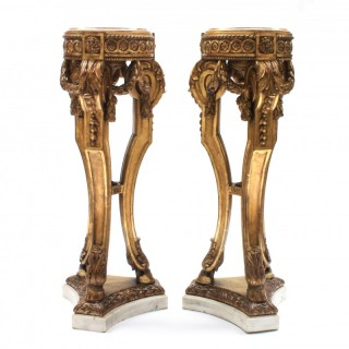 A pair of Louis XVI style carved giltwood tripod pedestals