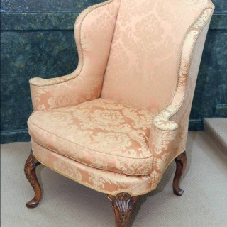 A fine Queen Anne walnut framed and upholstered wing chair