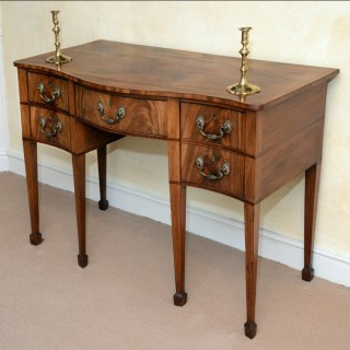 A rare small finely figured mahogany Sheraton period serpentine Sideboard