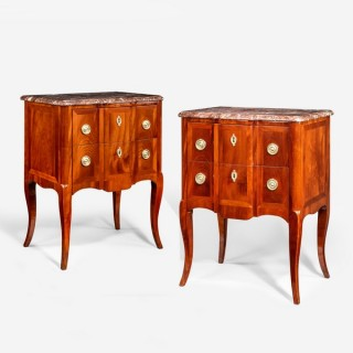 A pair of late 19th century flame mahogany petits commodes, each of breakfront form with two wide drawers with ring handles on slender cabriole legs, with a shaped marble top.