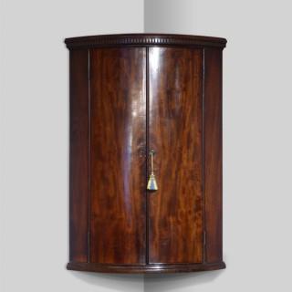 George III mahogany bowfront corner cupboard