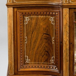This rosewood cabinet has a breakfront upper section with shelves and pigeon holes above a mirrored central section, all above a further cupboard and solid stretcher, inlaid in bone with scrolling arabesques and stringing.