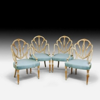 A set of 10 delicate Hepplewhite period armchairs with shield-shaped backs with triple splats carved with a coronet of stiff leaves from which emerge wheat ears and openwork twisted ribbons.