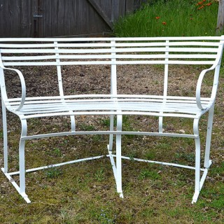 An early 20th century wrought iron semi-circular slat back garden seat