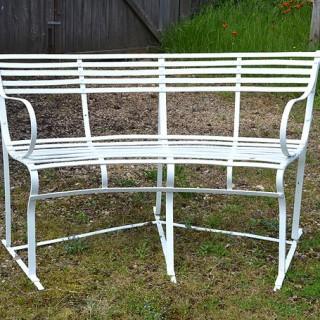 An early 20th century wrought iron semi-circular slat back garden seat