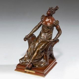 A bronze of an edwardian lady on a window seat