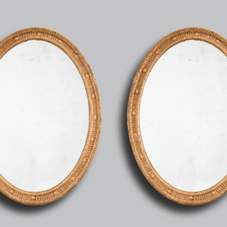 A pair of oval Adam giltwood mirrors