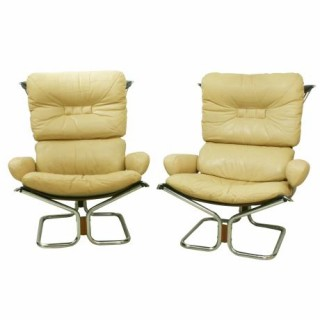 A pair of extremely comfortable arm chairs with cream leather covers designed by Ingmar Relling