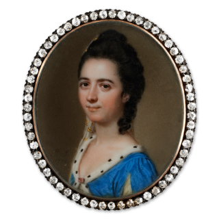 Portrait miniature of a Lady, identified as 'Miss Byron' wearing an ermine-trimmed blue dress slashed at the sleeves to reveal white and fastened with a jewel at the centre, her hair worn upswept with a hanging curl and decorated with an embroidered silk