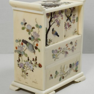 A MINIATURE JAPANESE IVORY AND SHIBAYAMA TABLE CABINET