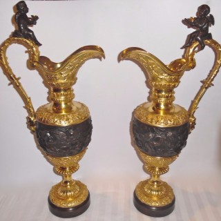 A pair of French patinated and gilt bronze bacchanal themed ewers