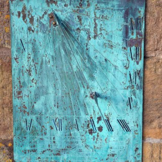 A modern Verdigris wall-mounted brass sundial plate with diagonal indicator