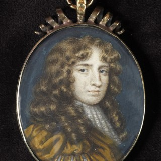 Portrait miniature of a Gentleman, wearing gold edged ochre doublet slashed at the sleeve to reveal white chemise, white stock and lace jabot, natural wig