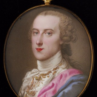 Portrait enamel of a Nobleman, wearing white, gold embroidered waistcoat, a scarlet-lined cloak over his shoulder, his hair worn en queue