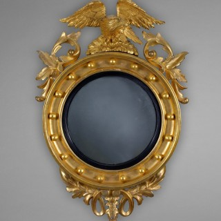Regency Period Carved Giltwood Convex Mirror surmounted by a traditional Eagle