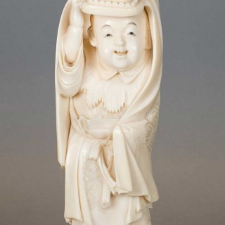 A CHARMING JAPANESE IVORY OKIMONO OF A BOY PERFORMING A LION DANCE