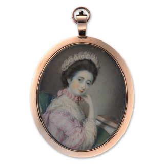 Portrait miniature of a young Lady, seated in a green chair, wearing pink and white sack back dress with ruffled sleeves and bow, matching pink silk choker and white lace bonnet, books on the table in front of her, c.1760
