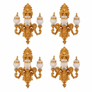 Set of four gilt bronze mounted frosted glass three-light wall lights