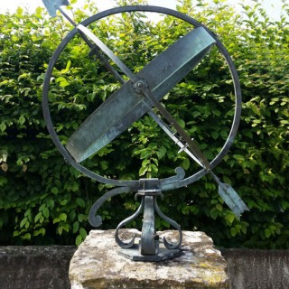 A mid- century brass armillary sphere raised upon a scroll base