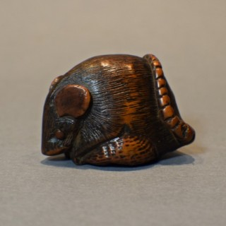 A JAPANESE BOXWOOD NETSUKE DEPICTING A RAT CLUTCHING A CHESTNUT