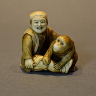 A CHARMING JAPANESE IVORY OKIMONO OF A SEATED MONKEY & SARUMAWASHI- SIGNED