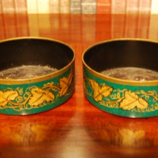 Pair of early 19th. century Toleware decanter coasters with gilt vine decoration on a green ground