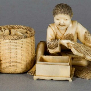 A FUN JAPANESE IVORY OKIMONO OF A BOY WITH HIS TOYS