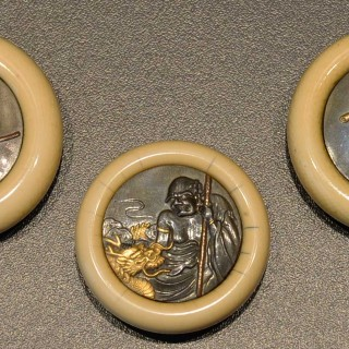 GROUP OF THREE JAPANESE KAGAMIBUTA IVORY AND MIXED METAL NETSUKES