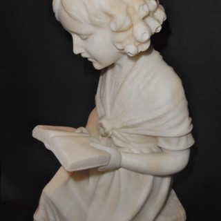 A French marble sculpture of a young girl reading