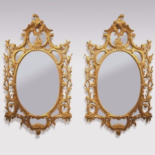 An important Pair of mid 18th Century oval giltwood Mirrors.