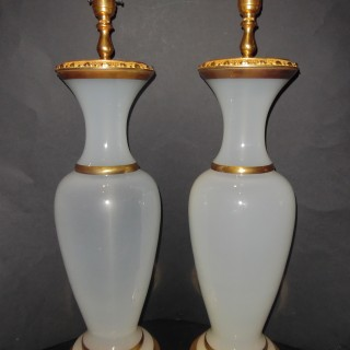 A pair of French ormolu mounted opaline glass lamps