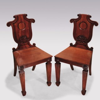 A pair of early 19th Century Regency period mahogany Hall Chairs.