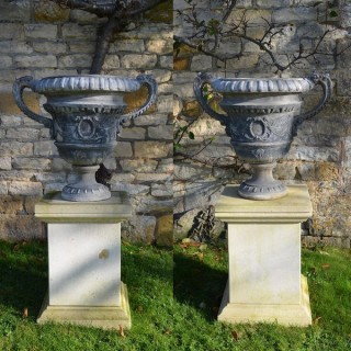 A pair of lead urns of campana form