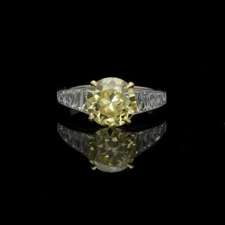 Hancocks Stunning 2.41 carat Fancy Intense Yellow Diamond Ring with tapering French-cut Diamond shoulders